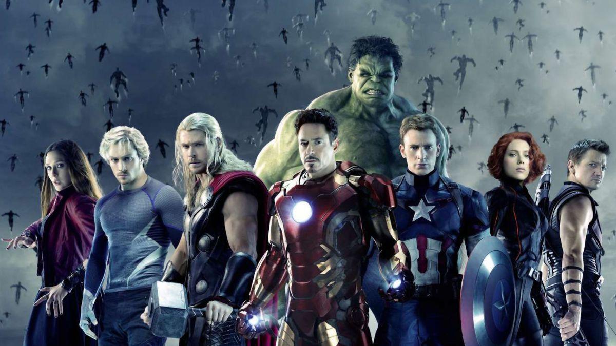 Die Avengers stehen Seite an Seite und blicken entschlossen in die Kamera, hinter ihnen steigen dunkle Konturen in Menschengestalt in die Höhe