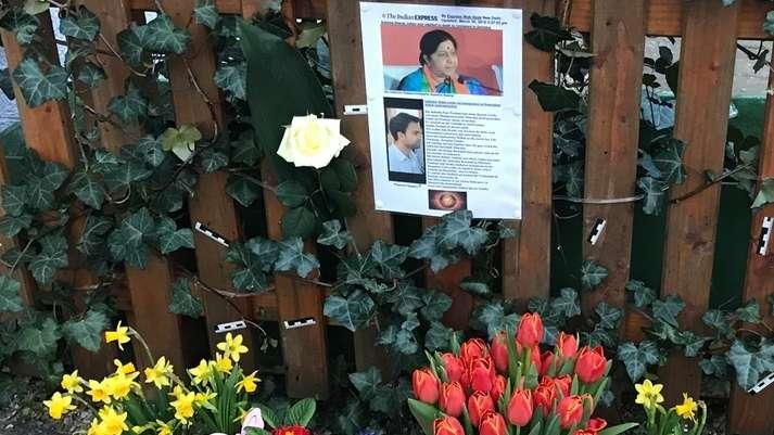 Blumen und Friedhofskerzen stehen vor einem Zaun an dem die Fotos der Opfer hängen.