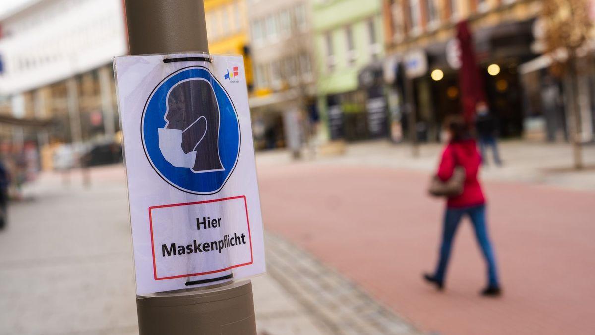 """Eine Frau geht an einem Plakat mit der Aufschrift """"Hier Maskenpflicht"""" vorbei."""