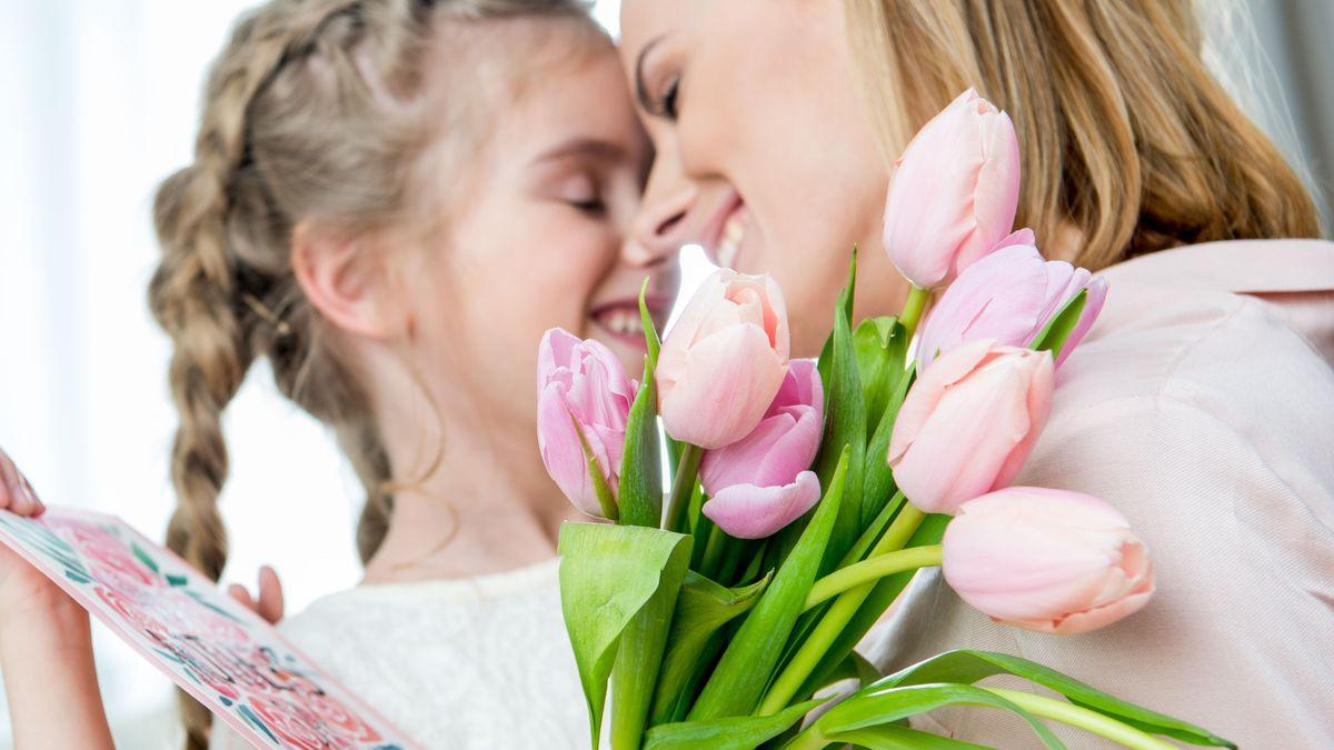 Kind überreicht Frau einen Tulpenstrauß