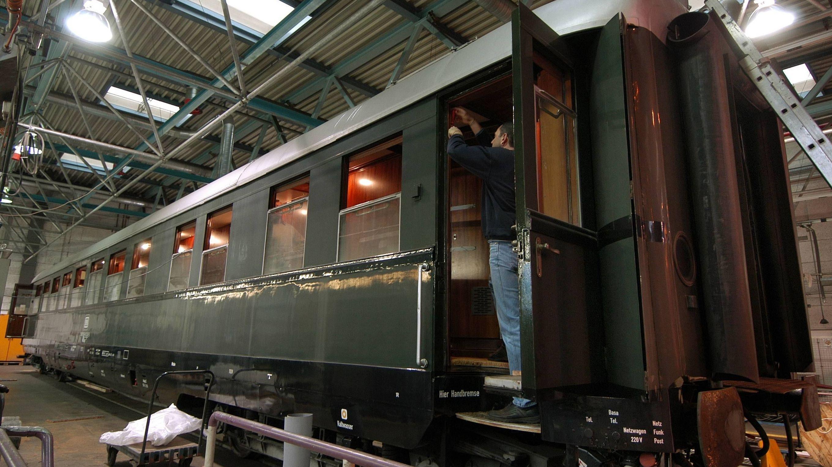 Ein Mann steht in einem alten Zugwaggon und restauriert ihn.