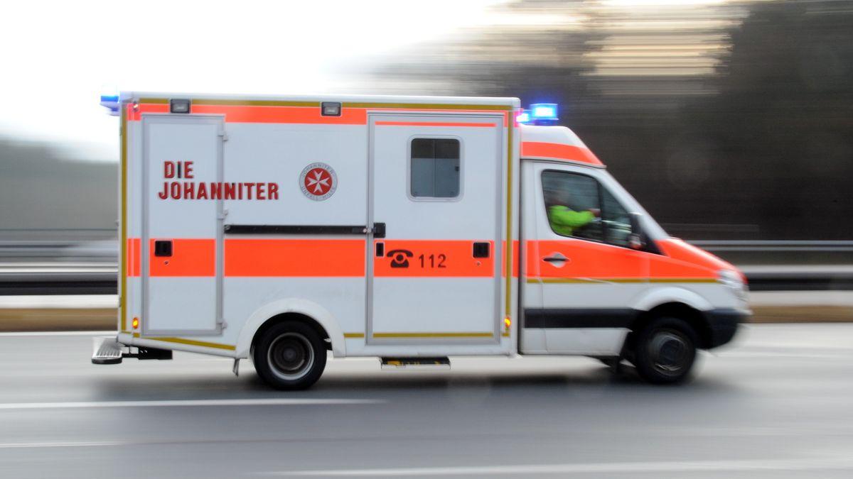 Ein Rettungswagen der Johanniter fährt mit Blaulicht auf einer Autobahn.