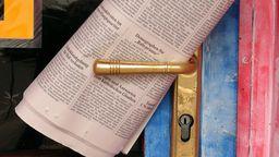 Eine Tageszeitung klemmt hinter einer blau-rot gestrichenen Tür | Bild:dpa/ picture alliance / JOKER