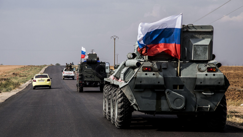 Truppen des russischenMilitärs fahren auf einer Straße in der Nähe syrisch-türkischen Grenze Patrouille.