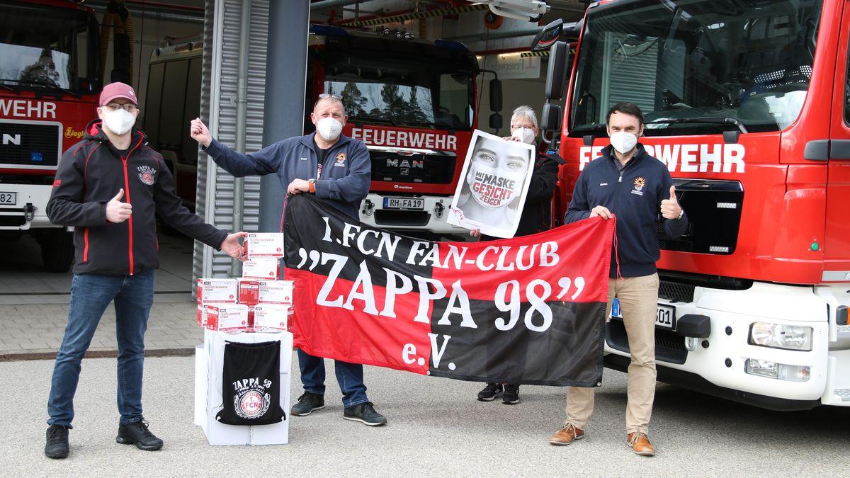 """Club-Fans mit Maske und Fan-Flagge """"Zappa 98"""" vor Feuerwehrautos."""
