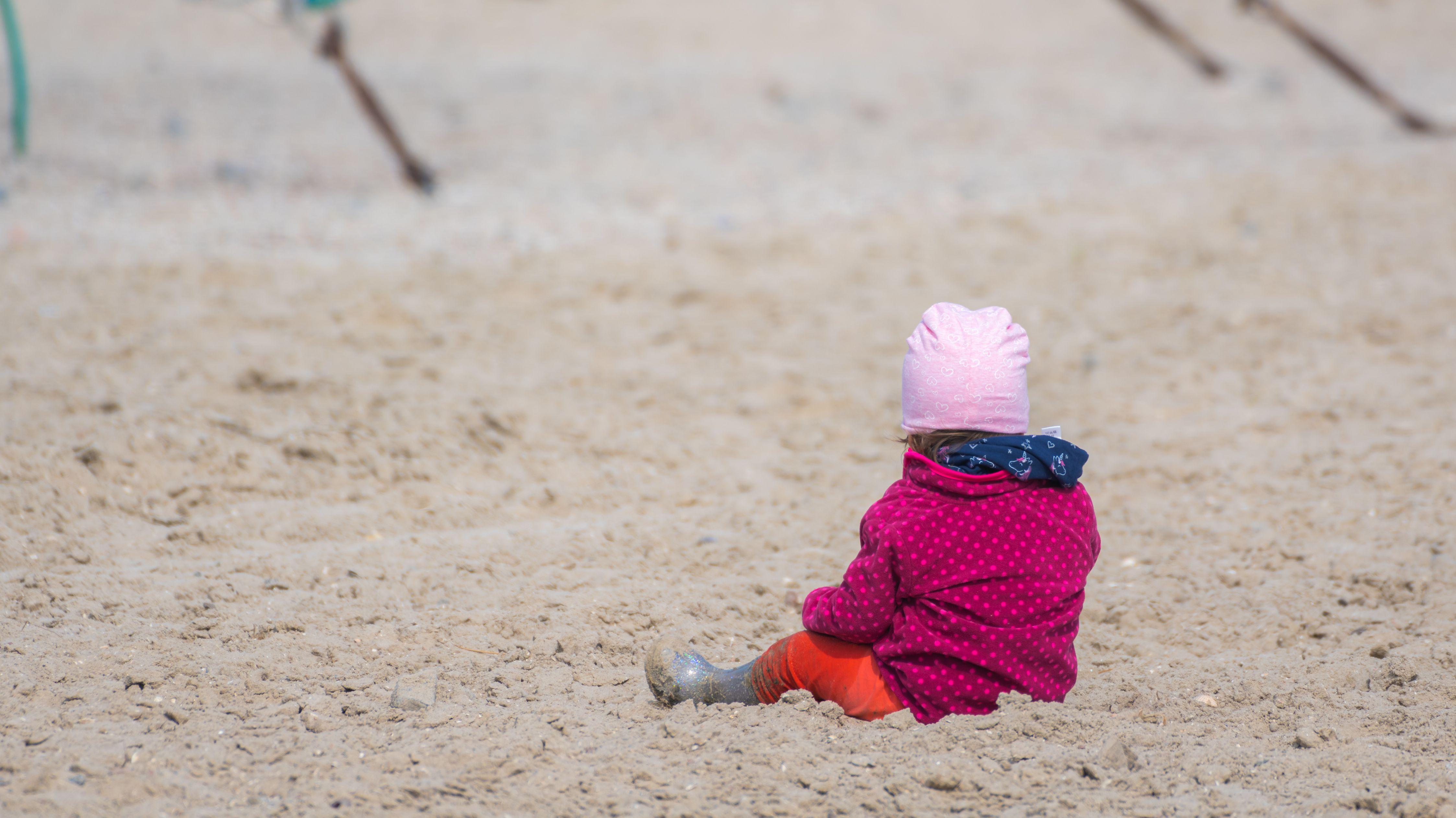 Ein kleines Kind sitzt im Sand
