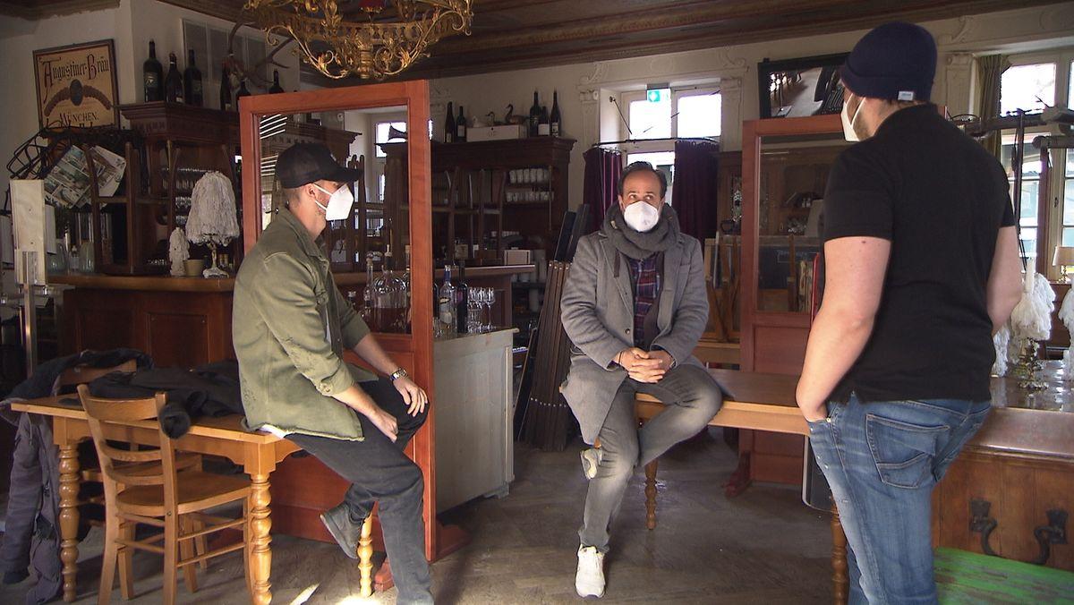 Drei Menschen mit Maske besprechen sich in einem Gastronomiebetrieb.