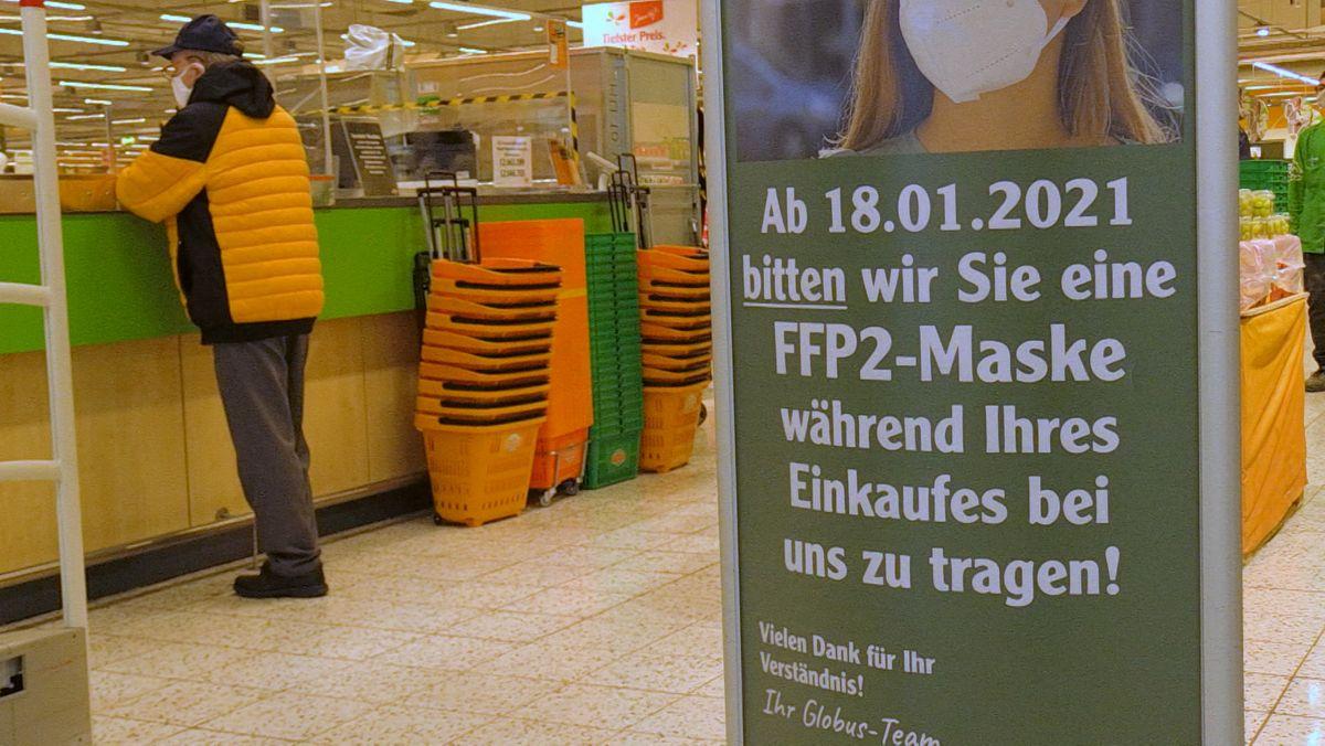 Kunde in einem Supermarkt - daneben Plakat, das auf die Pflicht zum Tragen einer FFP2-Maske hinweist
