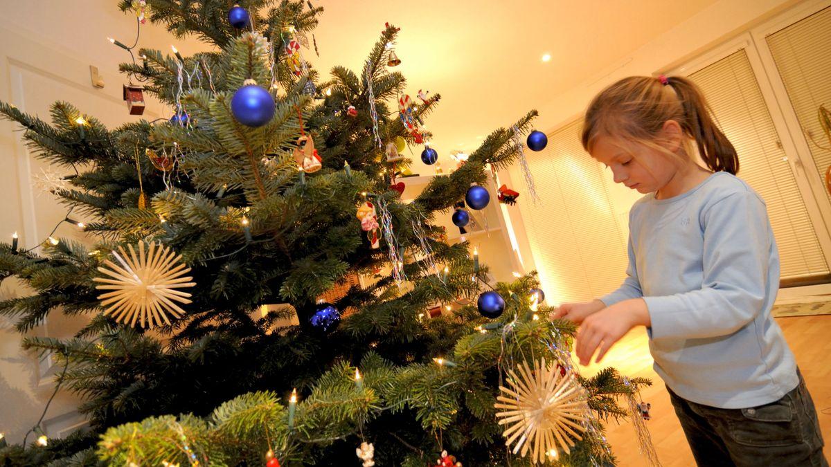 Kind schmückt Weihnachtsbaum