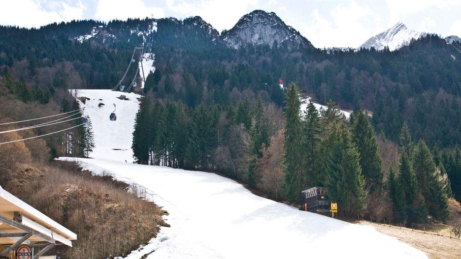 Die verschneite Kandahar-Skiabfahrt am Kreuzeck bei Garmisch-Partenkirchen. Über der Piste schweben die Gondeln der Kabinenbahn. Links und rechts der Strecke sind die Hänge schneefrei.