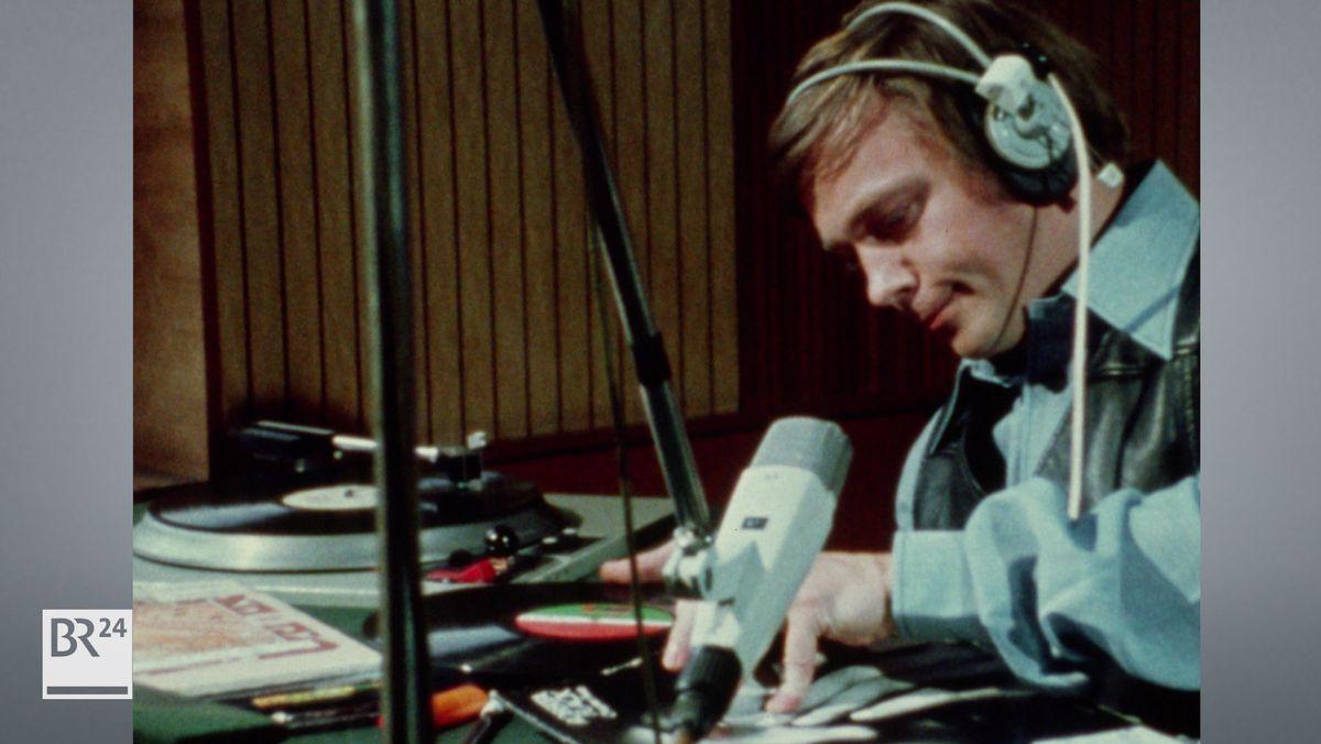 Mann am Mikrofon mit Schallplatten