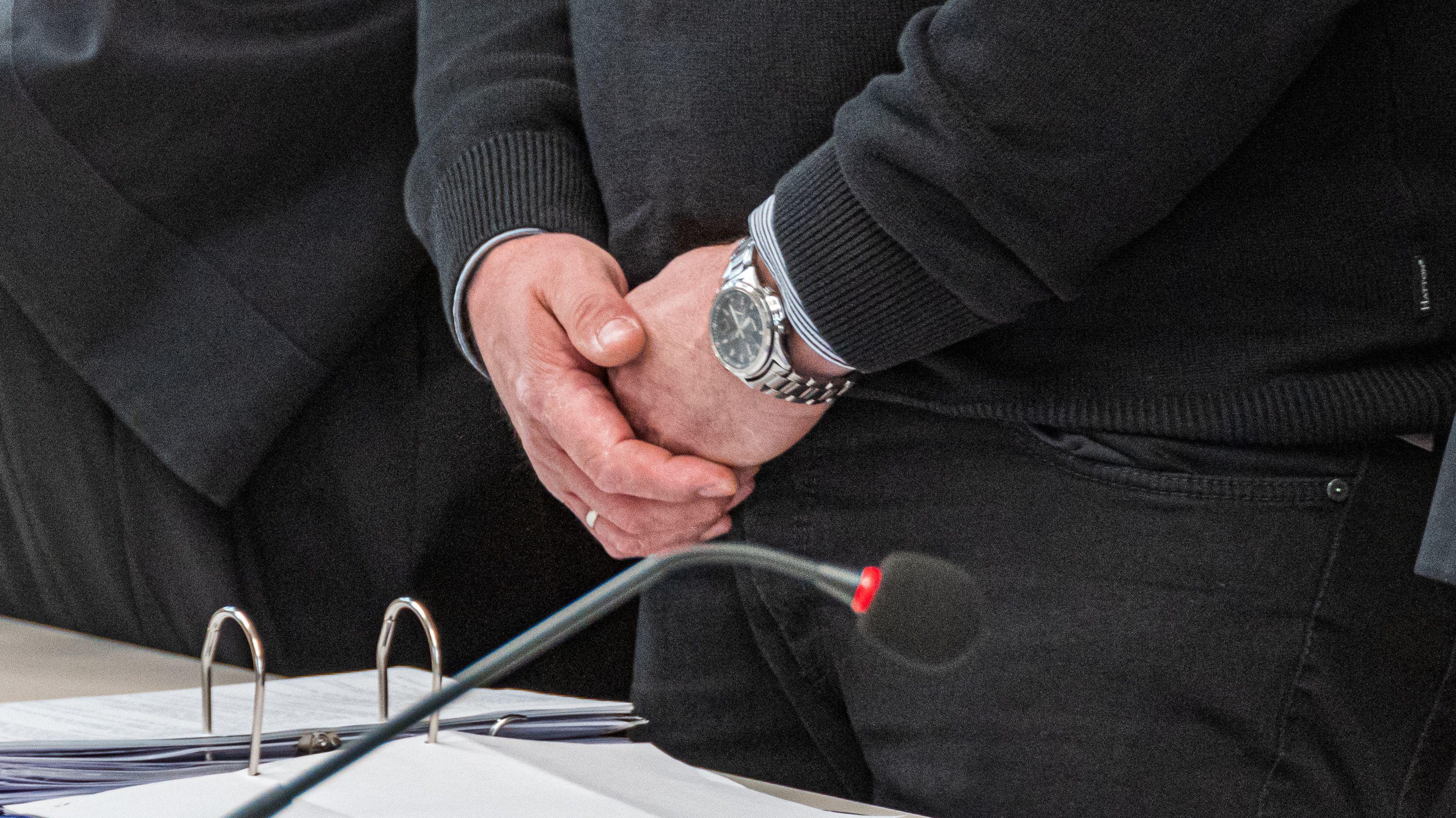Der Angeklagte steht mit verschränkten Händen im Verhandlungssaal des Landgerichts Amberg
