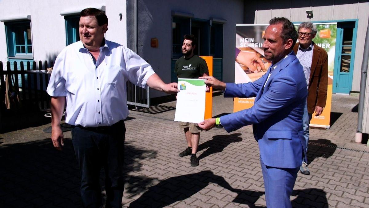 Die Schreinerinnung Mittelfranken Mitte bekommt von Umweltminister Thorsten Glauber eine Urkunde überreicht.