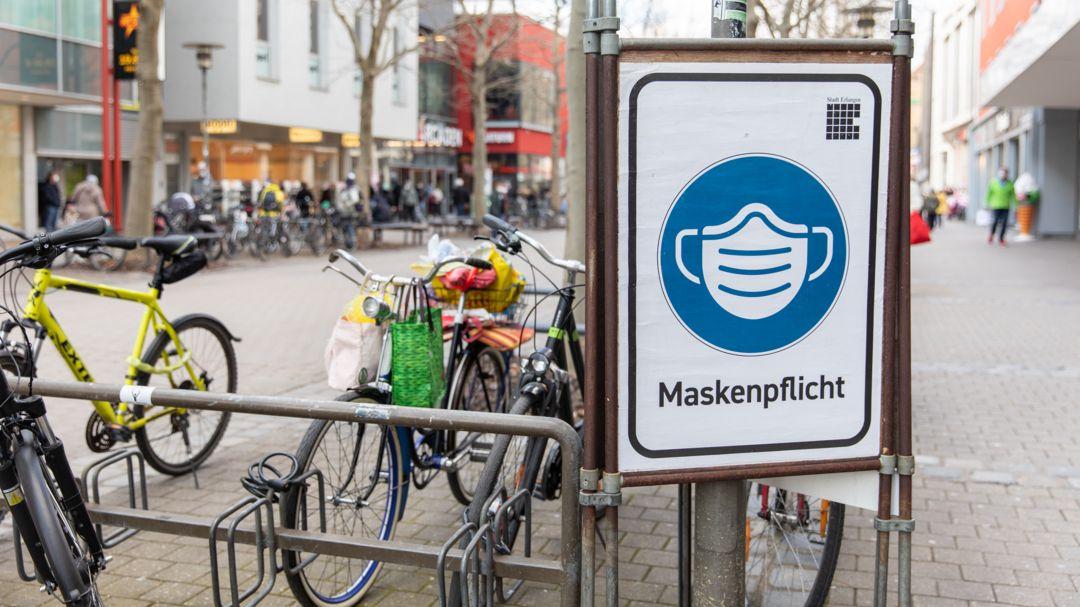 Ein Schild der Stadt Erlangen, das auf die geltende Maskenpflicht hinweist.