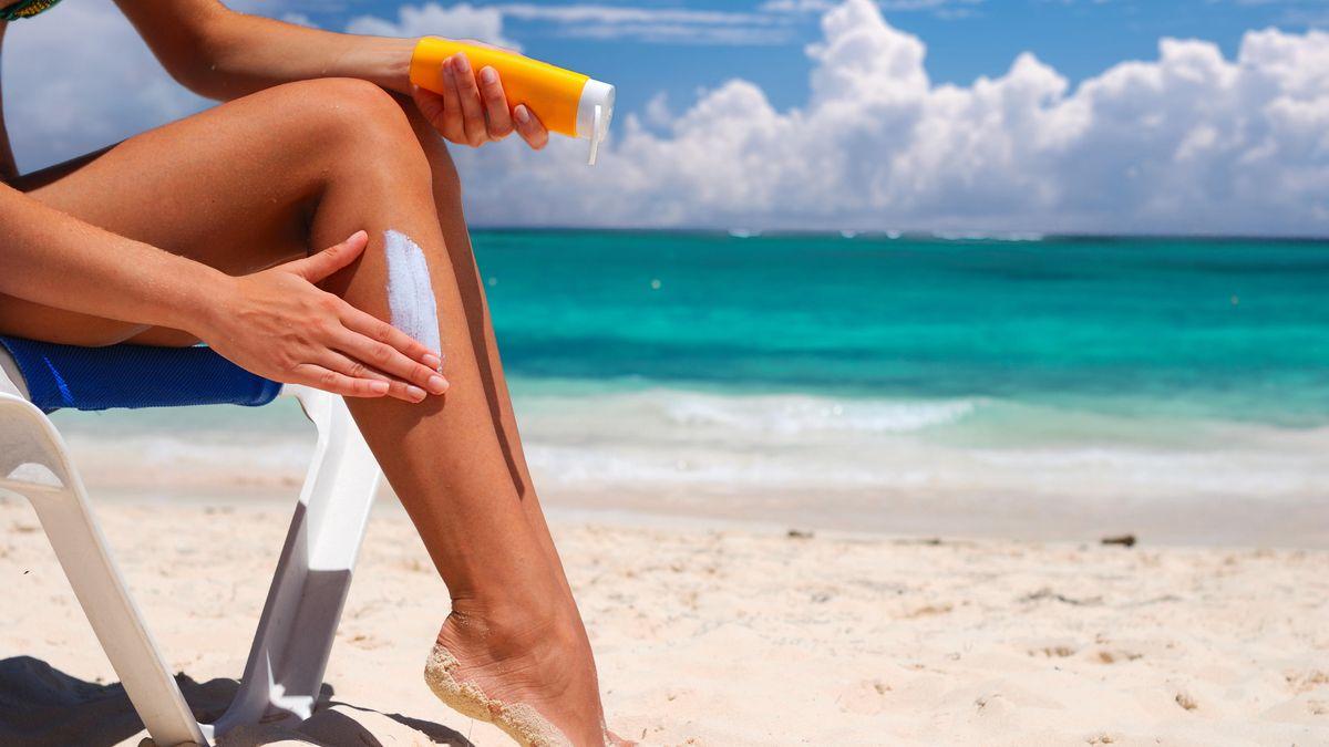 Eine Frau cremt ihr Bein am Strand mit Sonnencreme ein.