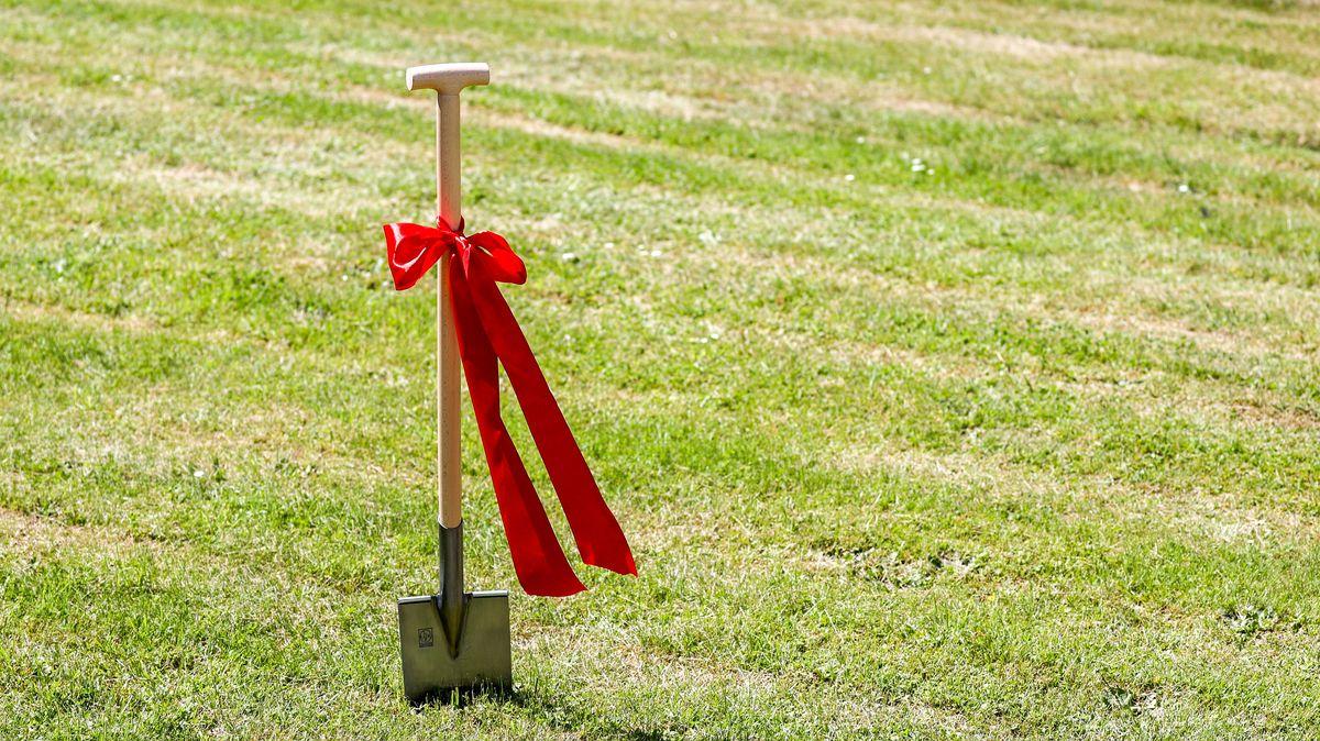 Ein mit einer roten Schleife geschmückter Spaten steht vor einem Spatenstich auf einer Wiese.