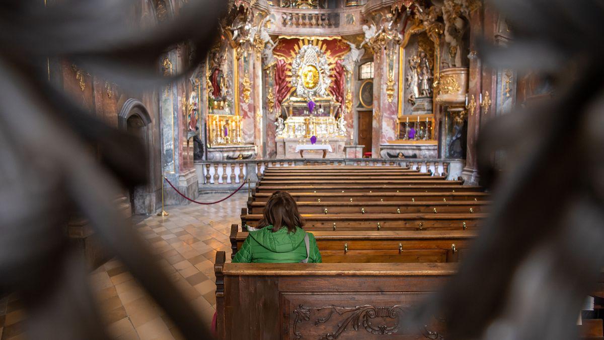 Eine Frau sitzt in einer Kirchenbank der Asam-Kirche in der Münchner Fußgängerzone.