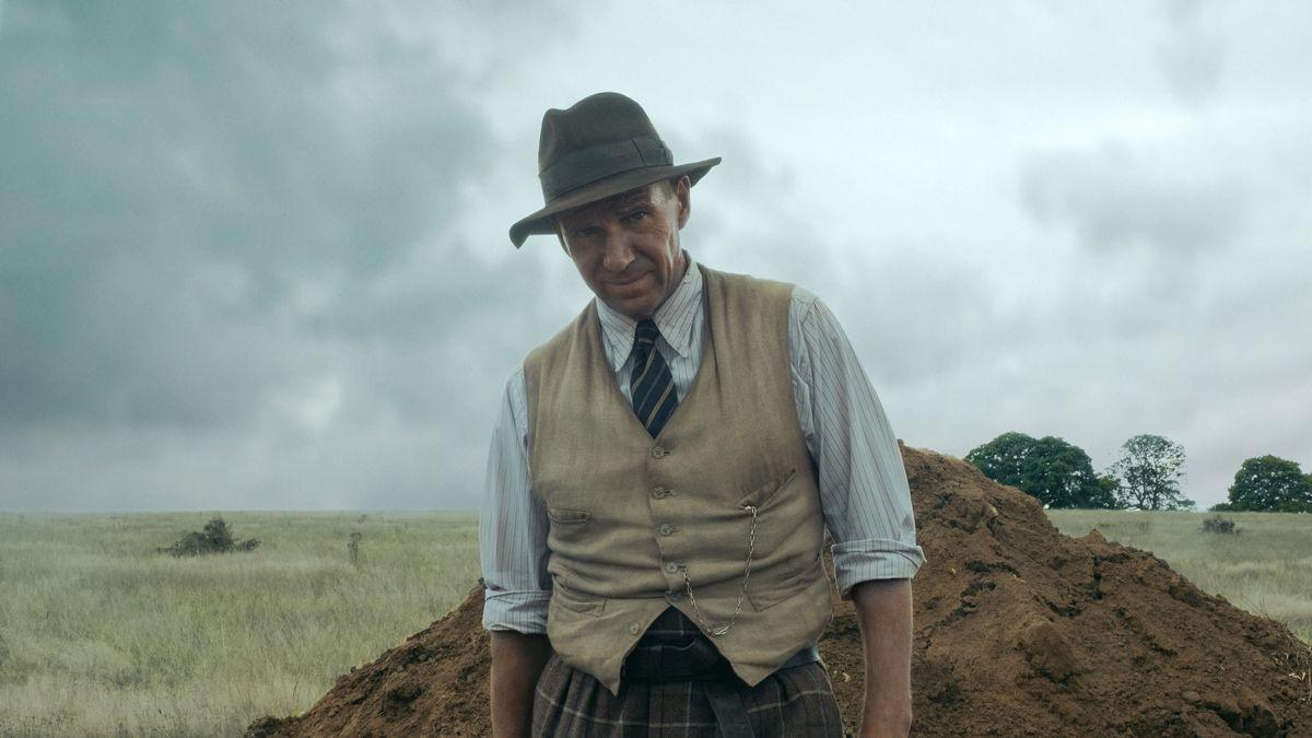 Ein Mann mit Hut steht vor einem aufgeschütteten Erdhaufen.