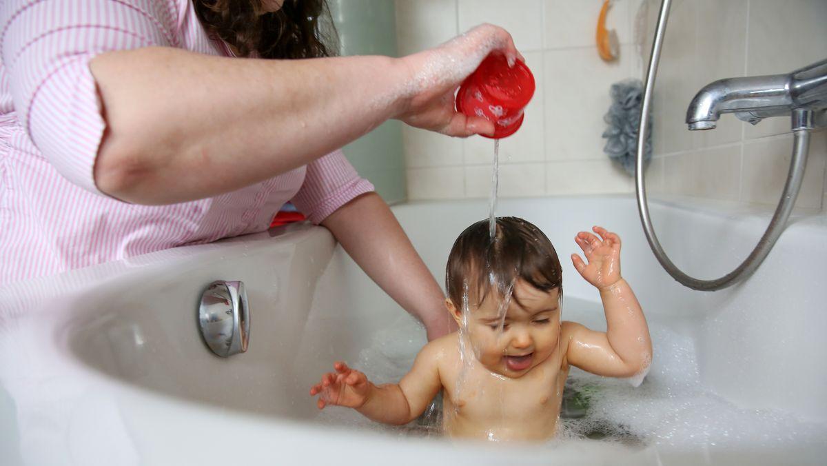 Mutter schütter Kind in der Badewanne Wasser über den Kopf