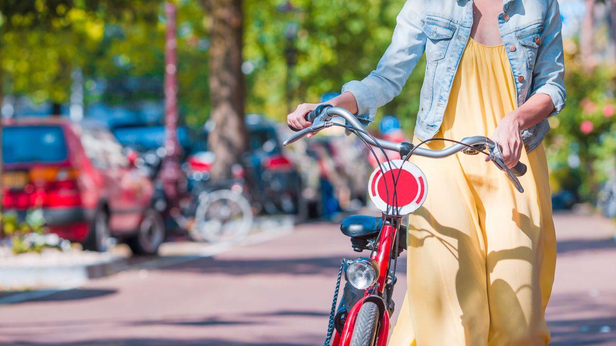 Frau schiebt ein Fahrrad auf der Straße