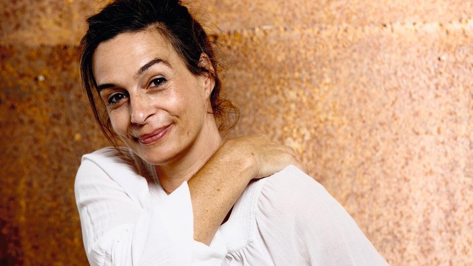 Autorin Alexandra Reinwarth lächelt, vor einer Wand stehend, in die Kamera