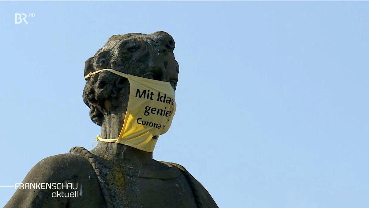 Heiligenfigur auf der Alten Mainbrücke in Würzburg mit Mundschutz