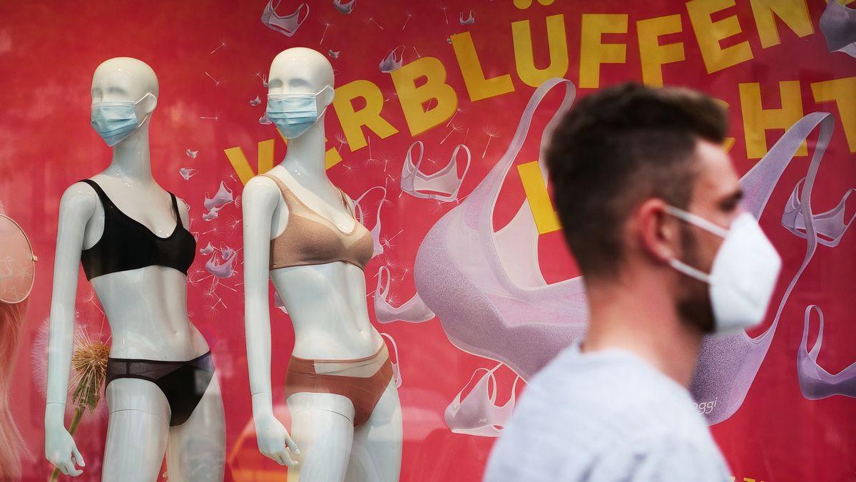 Mann mit Mundschutz vor Schaufenster mit Puppen