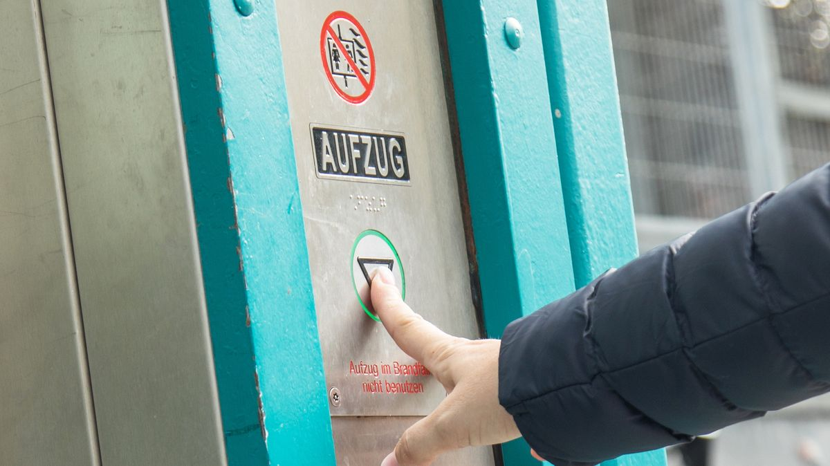 In einem Fahrstuhl drückt jemand den Knopf nach unten (Symbol)