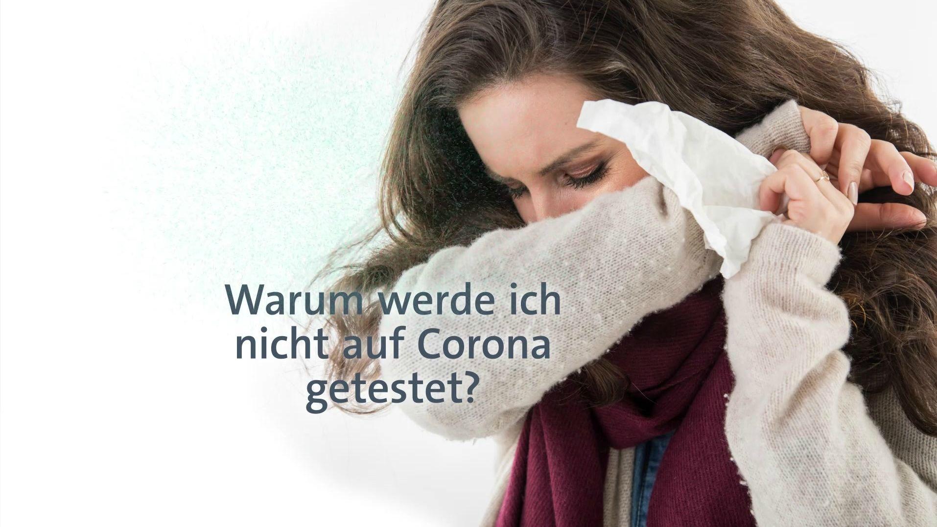 Eine Frau niest in ihren Pullover.