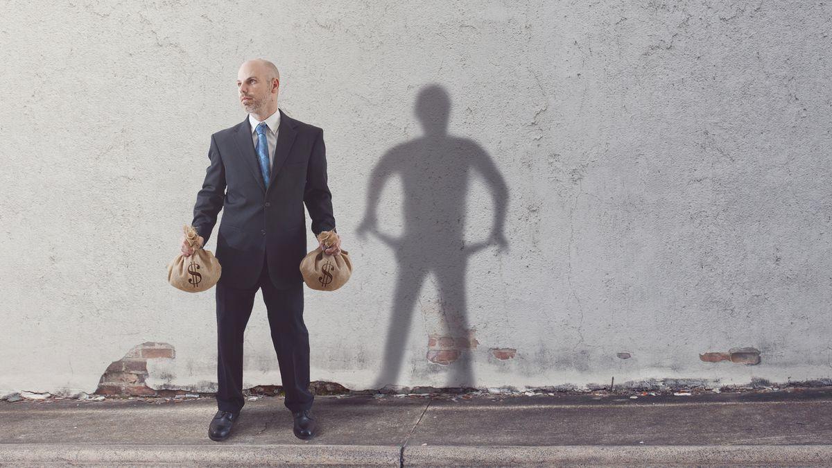 Ein Mann steht mit Geldsäcken auf der Straße, sein Schatten ist arm.