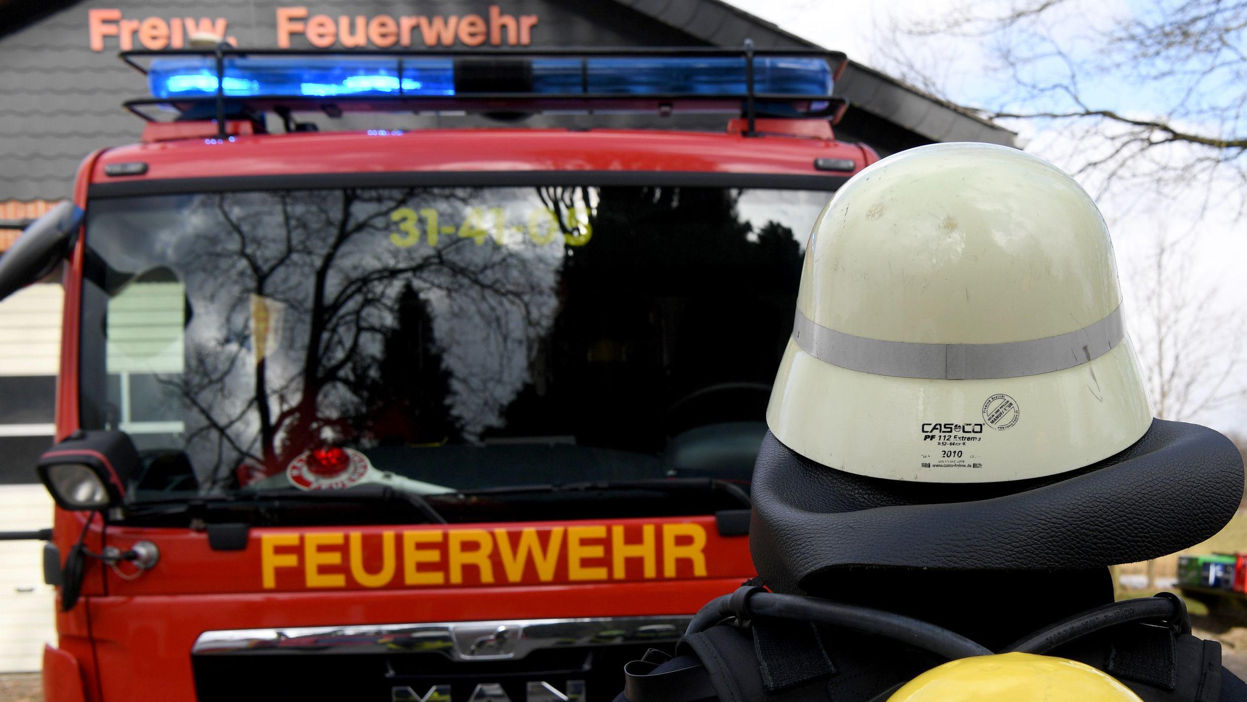 Feuerwehrmann steht vor Löschfahrzeug