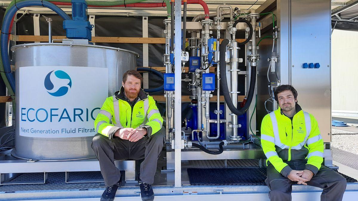 """Sebastian Porkert und Adrian Scholl, Gründer des Startups """"Ecofario"""", sitzen in gelben Warn-Jacken vor ihrer Anlage zur Mikroplastik-Filterung. Die Anlage steht auf der Grundfläche eines PKW-Anhängers. Links ein großer Abwassertank mit dem Firmenlogo, in der Mitte Schläuche, Rohre und Messgeräte, rechts ein Metallschrank mit Elektronik und Bedien-Monitor."""