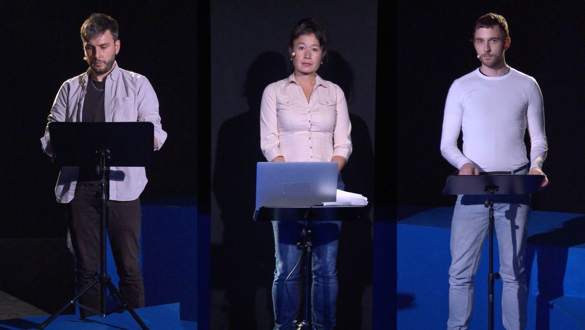 Drei Menschen an Sprechpulten nebeneinander geschaltet: Hito Steyerl: Mission accomplished Belangiege