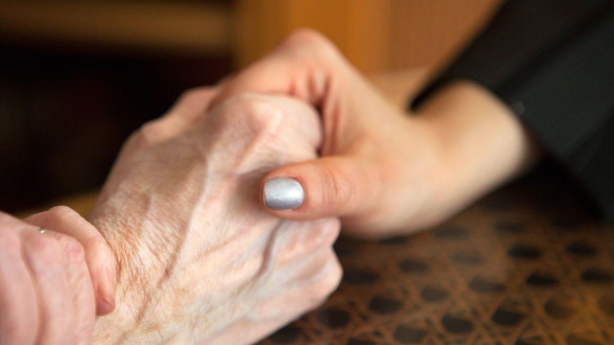 Ein Frau hält die Hand ihrer Mutter (Symbolbild)
