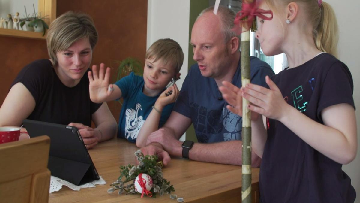 Eine vierköpfige Familie sitzt um ein Tablet.