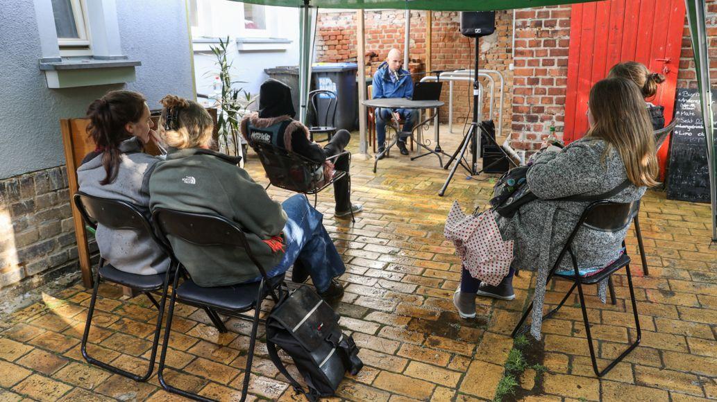 Unter einer grünen Plane hören fünf Menschen einem Autor zu: Lesefest in Leipzig