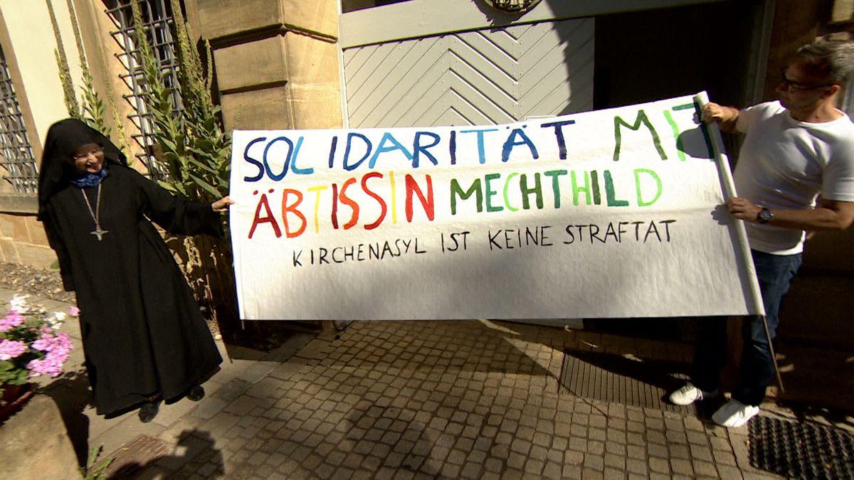 """""""Solidarität mit Äbtissin Mechthild"""" steht auf einem Transparent, das ein Mann und eine Ordensfrau halten."""