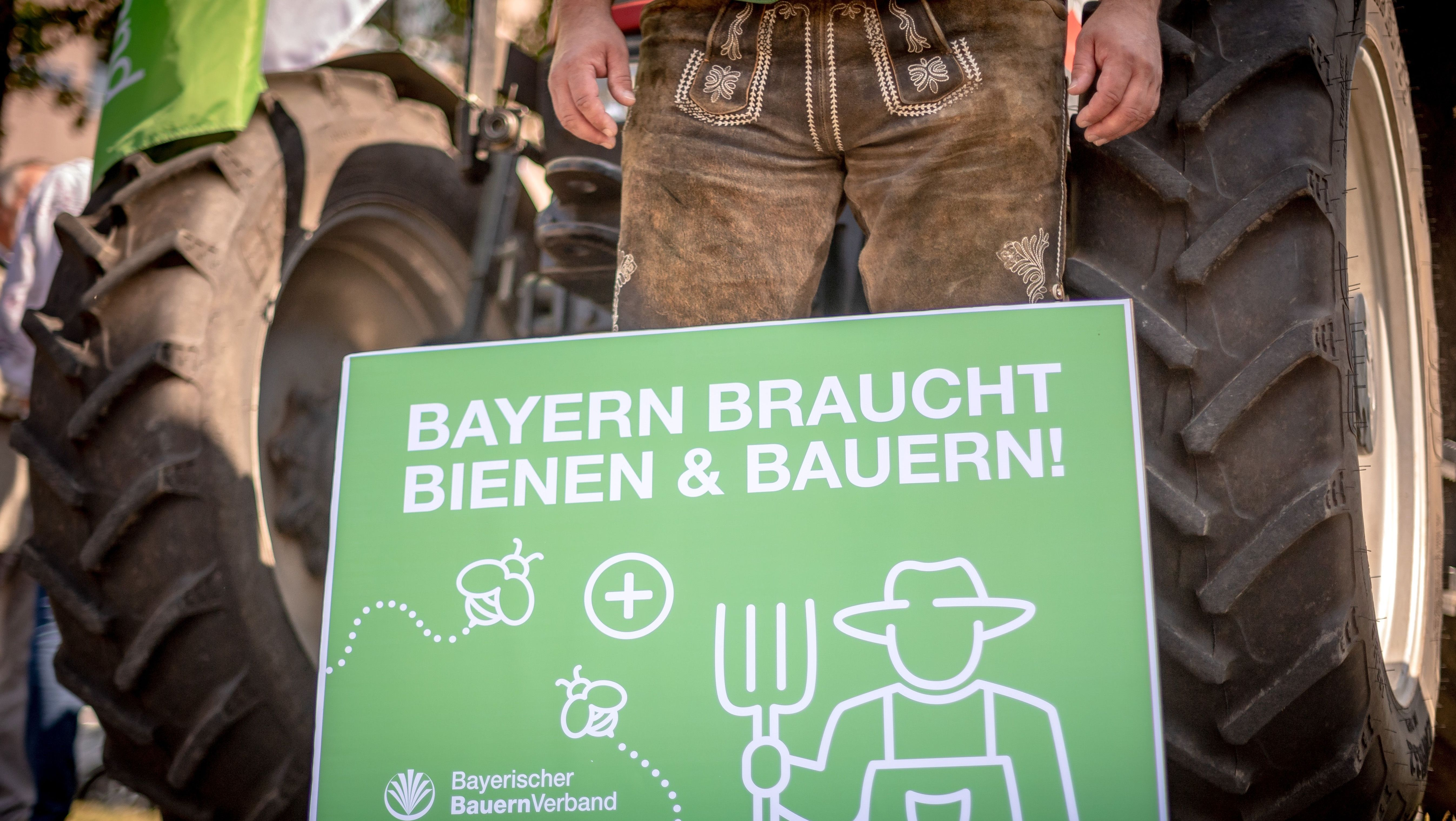 """Ein Mitglied des bayerischen Bauernverbandes mit einem Schild mit der Aufschrift """"Bayern braucht Bienen und Bauern"""""""
