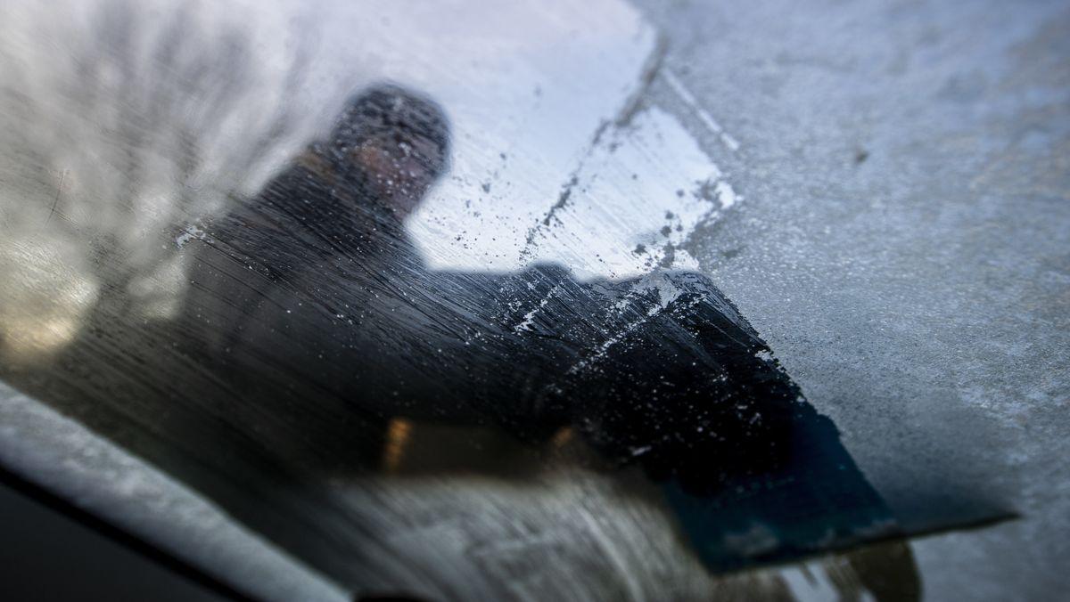 Autofahrer beim Eiskratzen