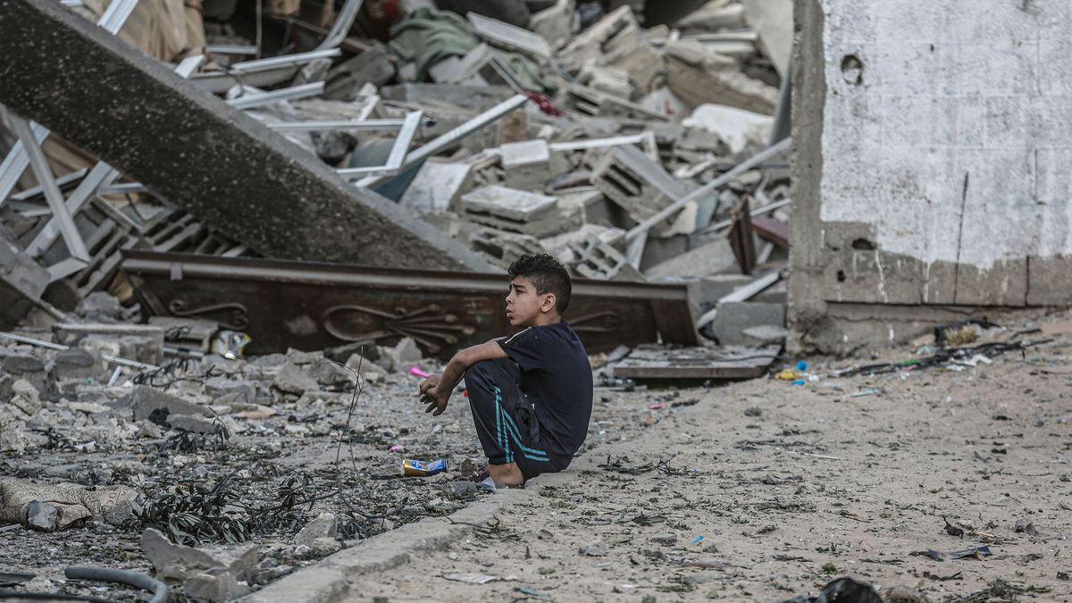 Ein Junge sitzt vor den Trümmern eines eingestürzten Wohnhauses, nachdem es am Morgen von einem israelischen Luftangriff getroffen wurde.