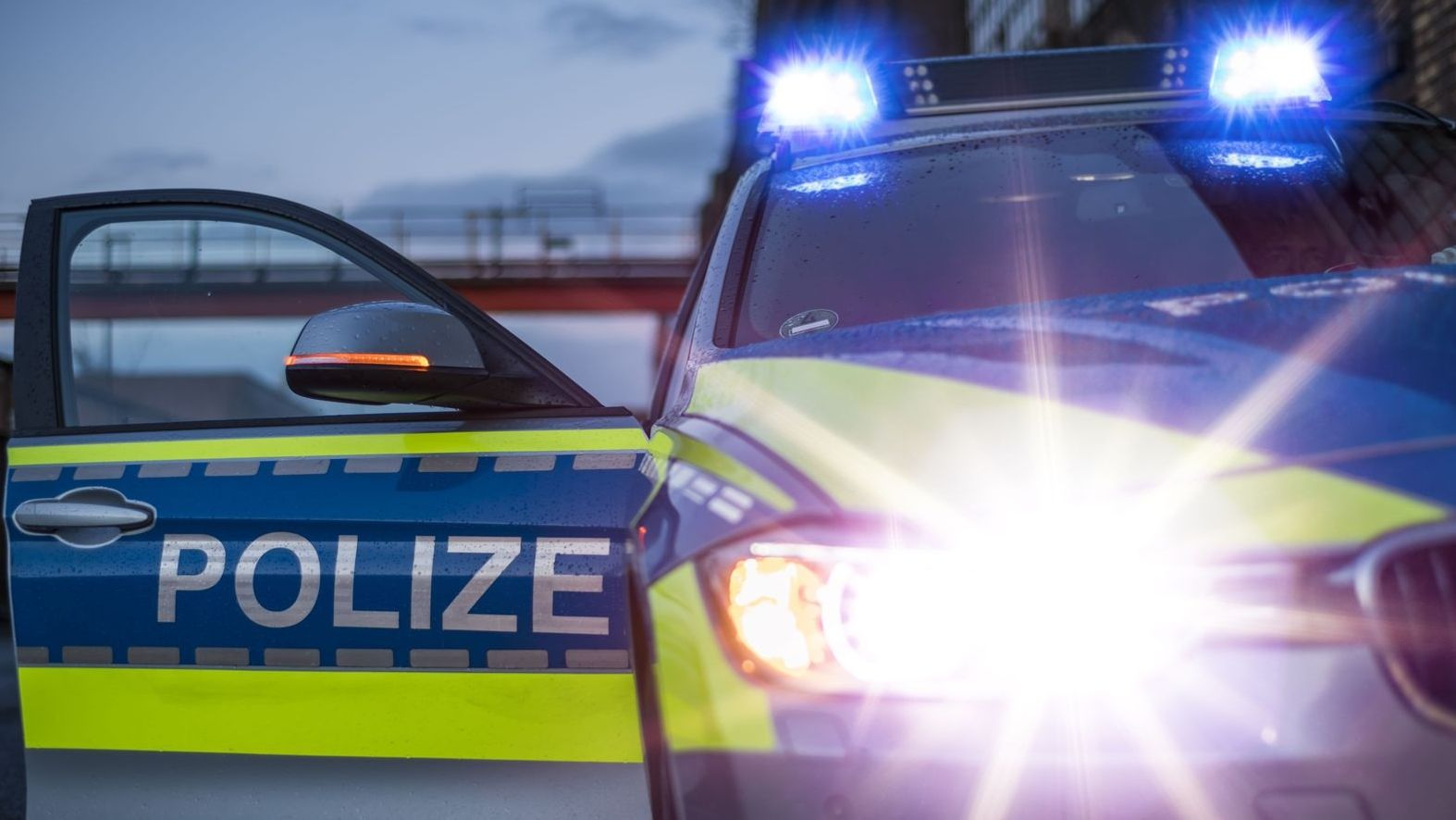 Ein Polizeiauto mit offener Tür und Blaulicht in Betrieb