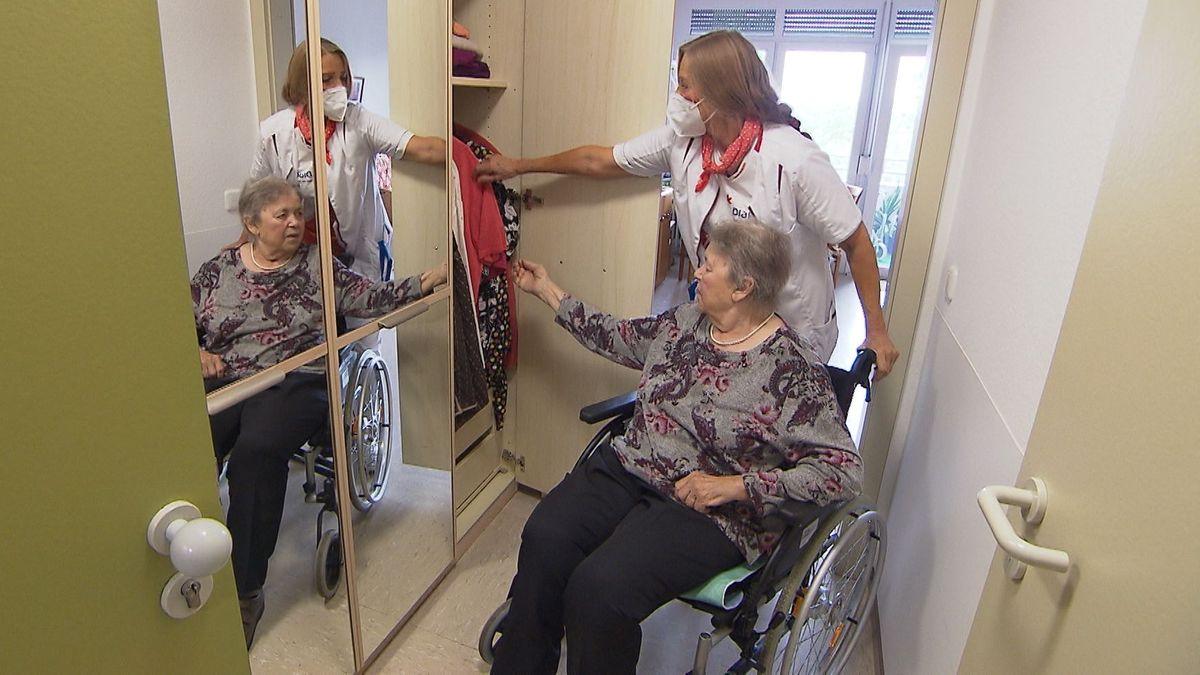 Pflegefachkraft Anna Maria Adämmer sucht mit einer Bewohnerin eine Jacke aus ihrem Schrank.