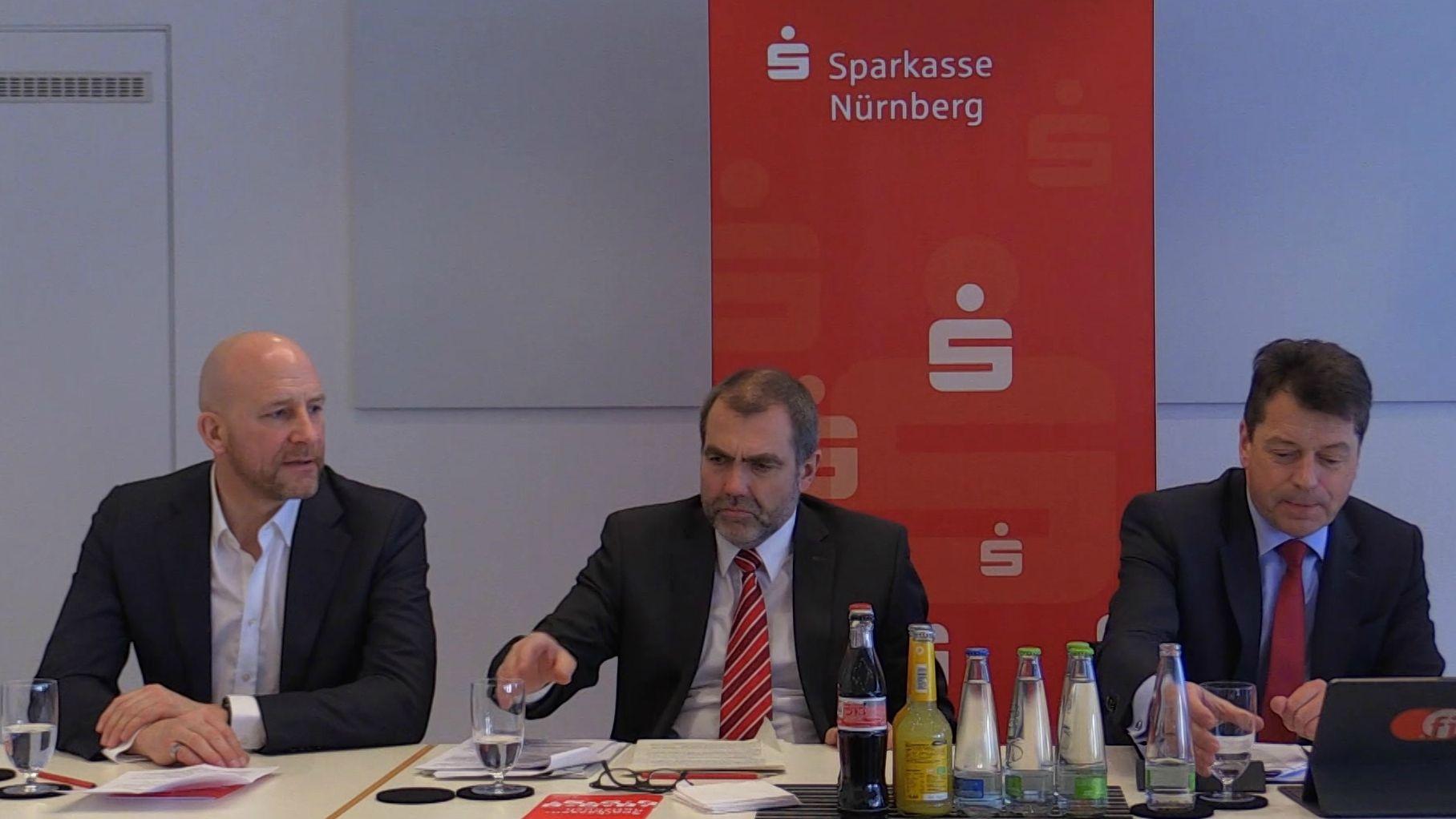 Drei Männer sitzen bei einer Pressekonferenz an Tischen, dahinter ein rotes Sparkassen-Transparent
