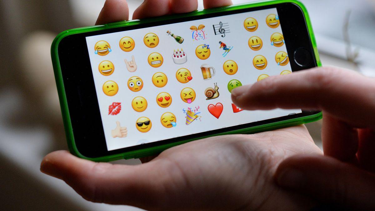 Eine Hand hält ein Smartphone, dessen Bildschirm Emojis zeigt.