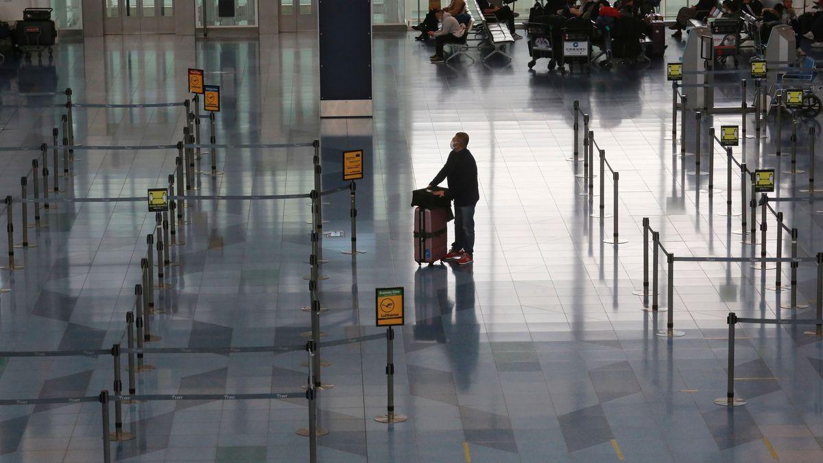 Ein Fluggast steht in der Abflughalle des internationalen Flughafens Haneda.