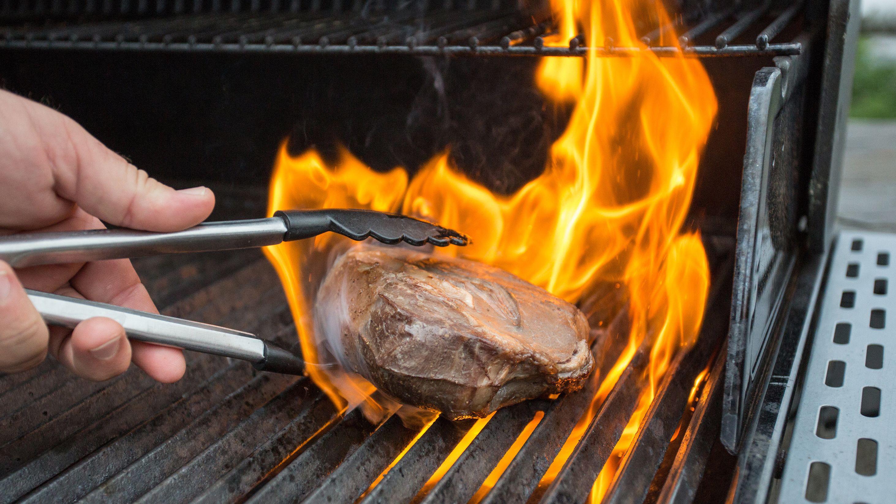 Ein Grillmeister nimmt Fleisch mit einer Zange vom Rost (Symbolbild).
