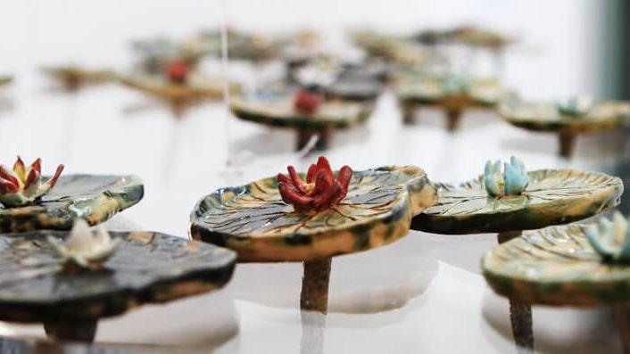 """Mehrere gefertigte Seerosen, die eine Vielzahl Schatten in alle Richtungen werfen: Die Installation """"Shadow Count"""" von Monika Lin"""