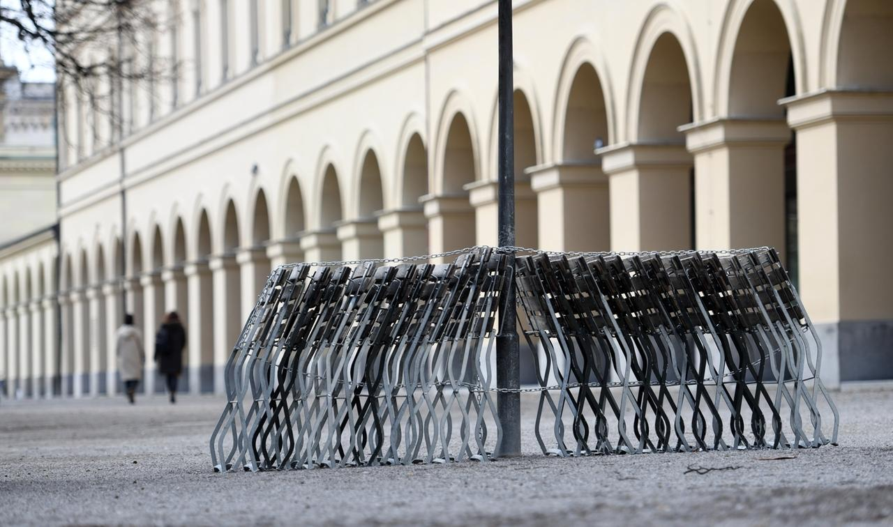 20.03.2021, Bayern, München: Biergartenstühle stehen im Hofgarten aufgereiht und angekettet an einer Laterne gelehnt. Foto: Tobias Hase/dpa +++ dpa-Bildfunk +++