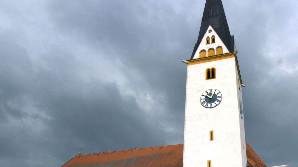 Die Kirche in Straßkirchen vor dunklen Wolken