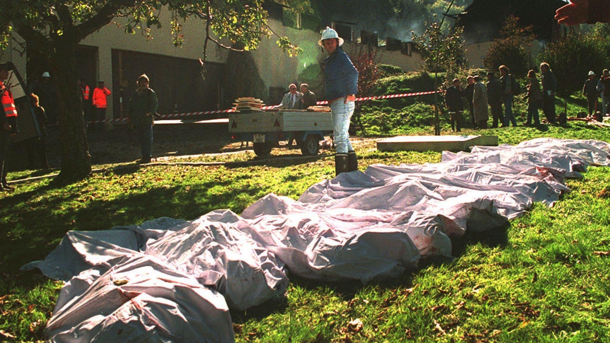 Polizei und Feuerwehr bergen im Oktober 1994 im schweizerischen Cheiry mehrere Leichen von Mitgliedern der Sonnentempler-Sekte.